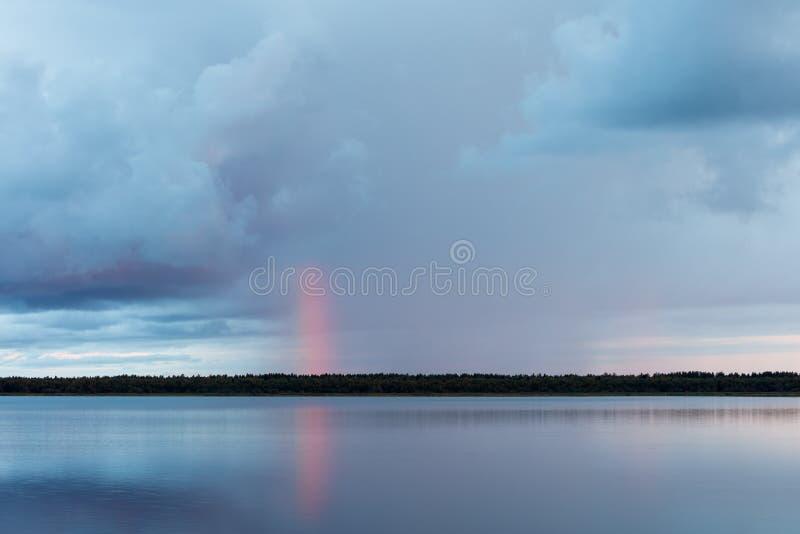 En dusch och en sällsynt röd regnbåge på soluppgång arkivbilder