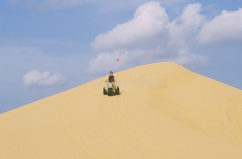 En dynbarnvagn för tre person som drar en skottkärra rider i lilla Sahara State Park i Oklahoma fotografering för bildbyråer
