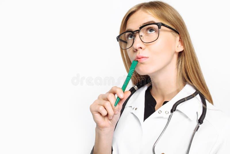 En eftertänksam doktor, en kvinnlig allmäntjänstgörande läkare med exponeringsglas, med en stethosco royaltyfri bild