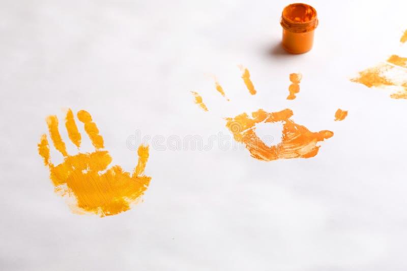 En el banco blanco del fondo con la pintura y las impresiones de las manos del ` s de los niños que dibujan con las manos imágenes de archivo libres de regalías