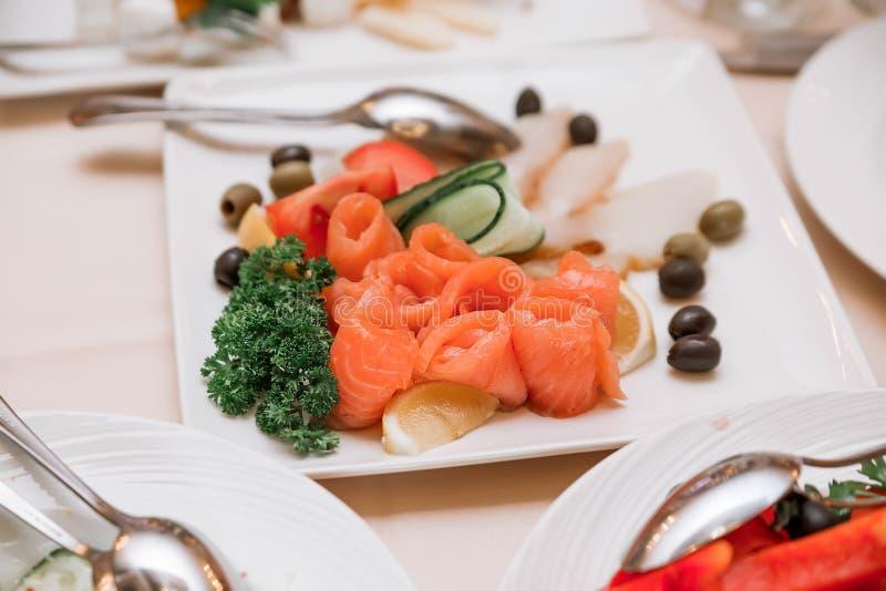 En el banquete hay una placa con los pescados rojos, aceitunas y aceitunas, adornadas con verdes fotografía de archivo