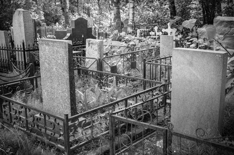 En el cementerio viejo hay sepulcros con las piedras sepulcrales y las cruces Imagen blanco y negro imágenes de archivo libres de regalías