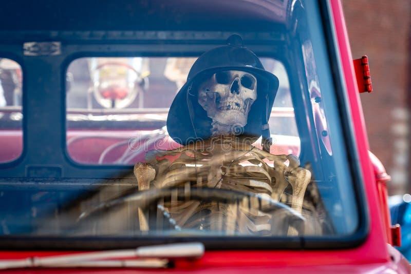 En el coche de bomberos viejo, un esqueleto humano con un casco del bombero es imagen de archivo libre de regalías