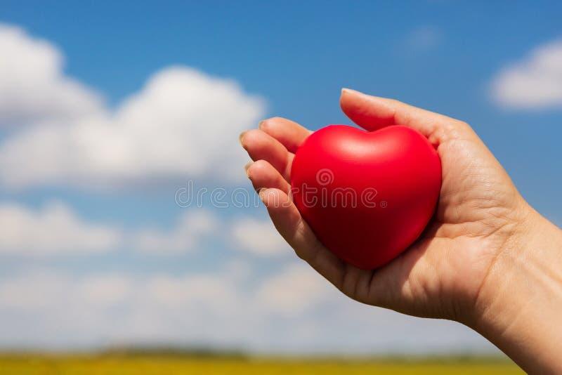 En el corazón rojo de la mano femenina, el concepto de vida y el amor, contra el cielo azul con las nubes imágenes de archivo libres de regalías