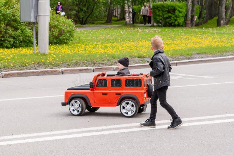 En el festival, los niños montan en los coches grandes del juguete imagenes de archivo