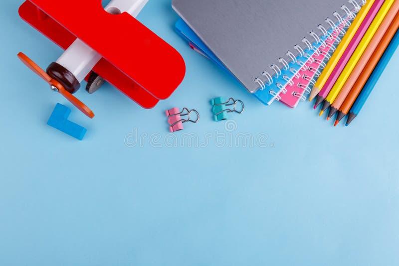 En el fondo azul son los cuadernos, los clips, los lápices coloreados, una tiza y un aeroplano rojo del juguete Visión superior fotografía de archivo libre de regalías