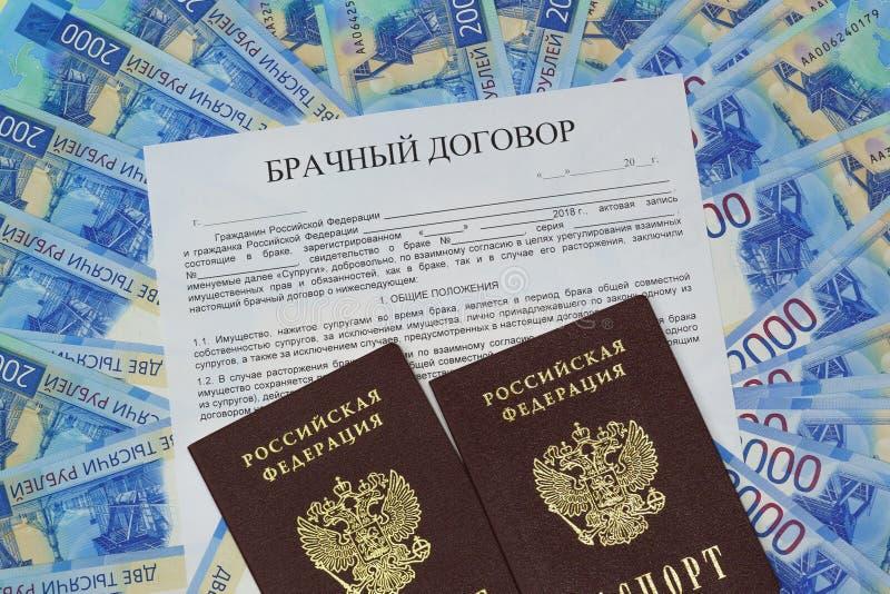 En el fondo de los nuevos billetes rusos es una forma del contrato de matrimonio y de dos pasaportes fotografía de archivo libre de regalías