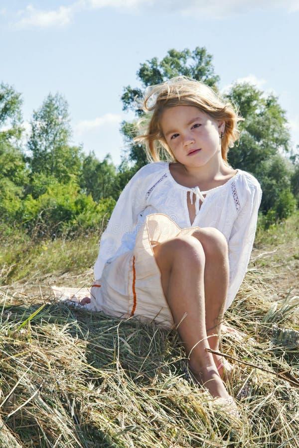 En el heno sienta a una niña y estar triste imagen de archivo