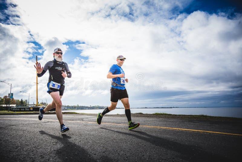 En el hombre joven y viejo que hace el maratón completo imágenes de archivo libres de regalías
