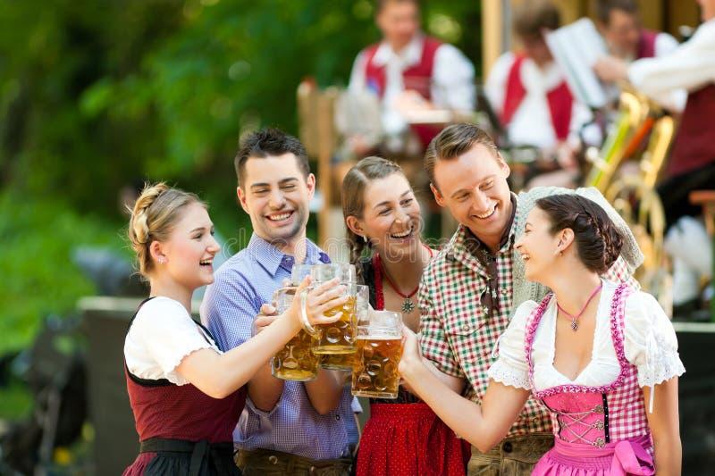 En el jardín de la cerveza - amigos delante de la venda fotografía de archivo