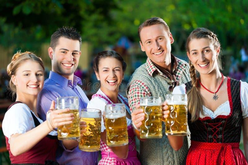 En el jardín de la cerveza - amigos que beben la cerveza fotografía de archivo