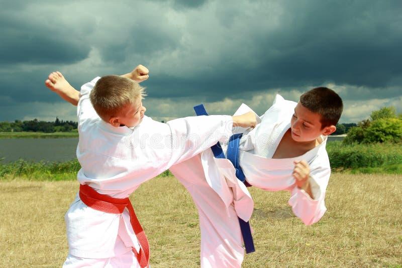 En el kimono dos los atletas están golpeando el brazo y la pierna en el cielo tempestuoso del fondo foto de archivo
