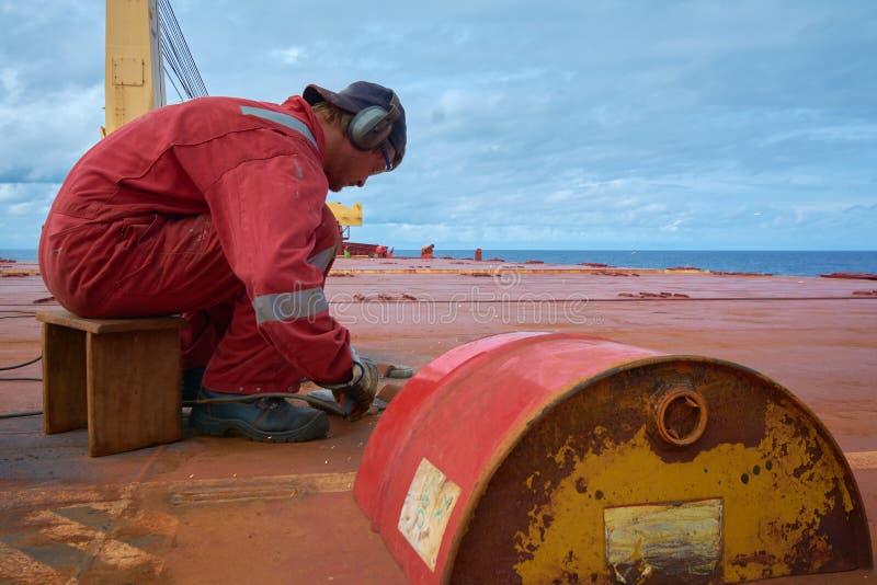 En el mar - circa octubre de 2018: Marineros que cortan los anillos en D viejos en la cubierta abierta de una nave Concepto de ma fotografía de archivo libre de regalías