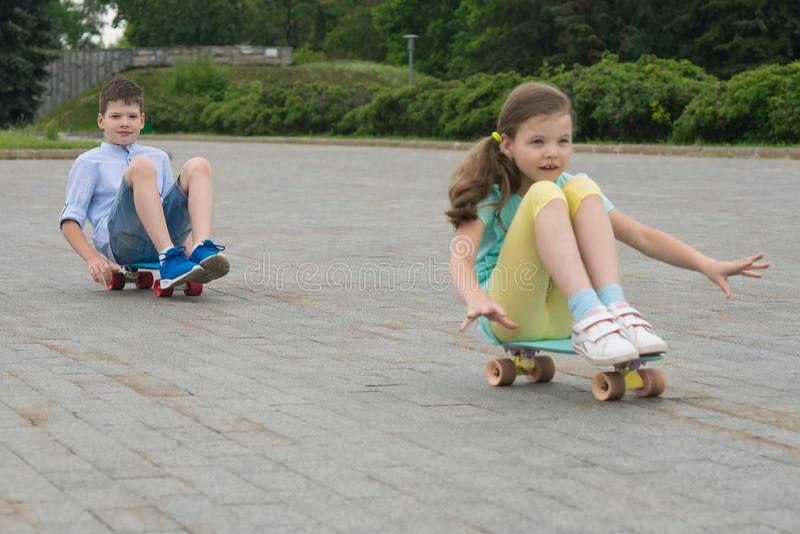 En el parque, al aire libre, un muchacho y una muchacha que montan un monopatín, sentándose en él, en los bloques de piedra fotografía de archivo libre de regalías