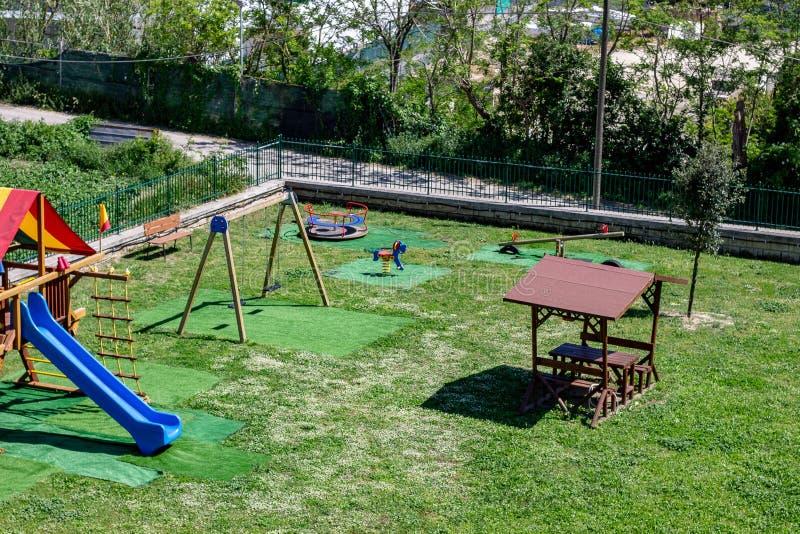 En el parque de los paseos de los niños, la diapositiva, el oscilación fotos de archivo libres de regalías