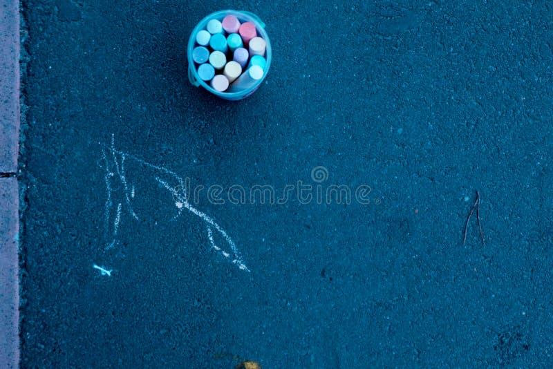 En el pavimento coloca un cubo de tiza y pintó algunas rayas en él imagenes de archivo