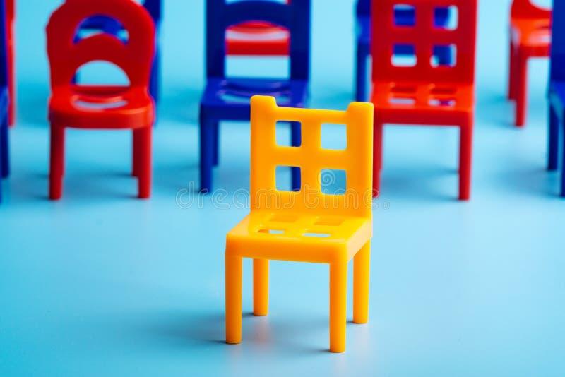 En el primero plano, una silla plástica amarilla, seguidos por otras sillas azules y rojas imágenes de archivo libres de regalías