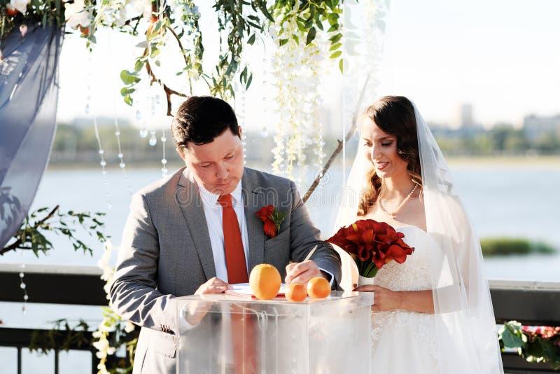 En el registro al aire libre de la boda la novia firma un documento de la boda imagen de archivo libre de regalías