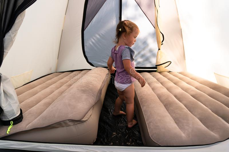 En el sitio para acampar, una niña en saltos de una tienda en los colchones fotos de archivo