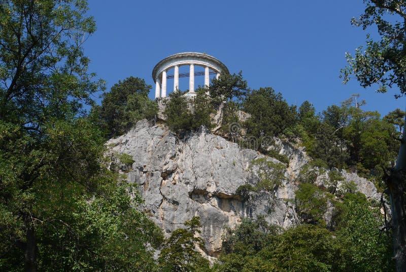 En el top de una colina rocosa está una construcción arquitectónica de una forma circular con las columnas del blanco contra imagen de archivo libre de regalías