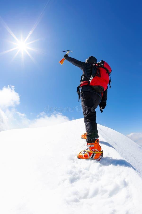 En el top: un escalador solo alcanza la cumbre de un pico de monta?a nevoso en la estaci?n del invierno foto de archivo