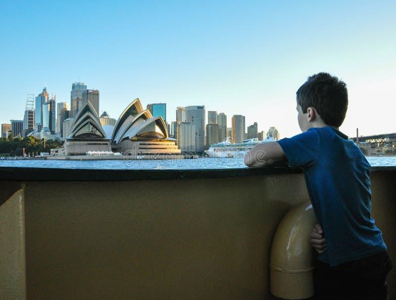 En el transbordador, el muchacho que mira a la casa de Sydney Opera en tiempo de verano hermoso fotografía de archivo