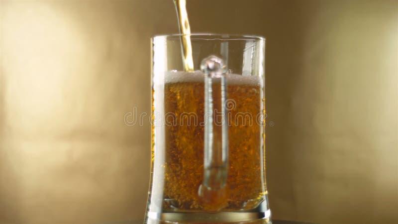 En el vidrio de una taza que cambie su eje, se vierte la cerveza, las cervezas de la cerveza se alza, un vidrio del primer imagen de archivo libre de regalías
