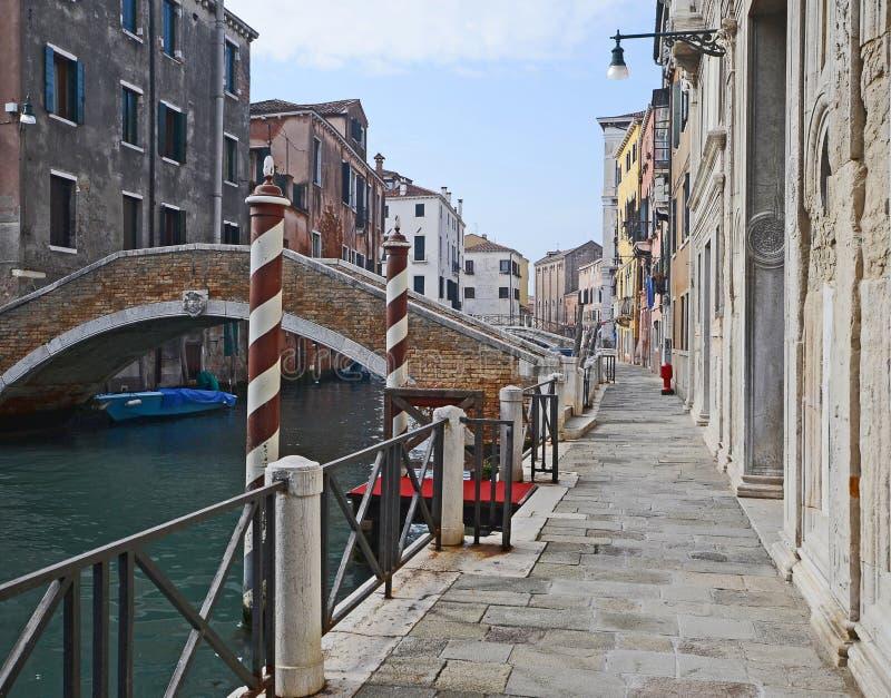 En elasticitet av en kanal i Venedig med fartyg och färgrika byggnader på en vinterdag royaltyfria bilder
