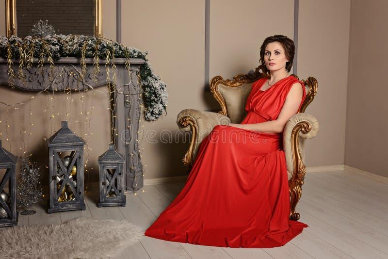 En elegant brunettflicka i en röd klänning sitter i en stol i sagolika nytt års inre fotografering för bildbyråer