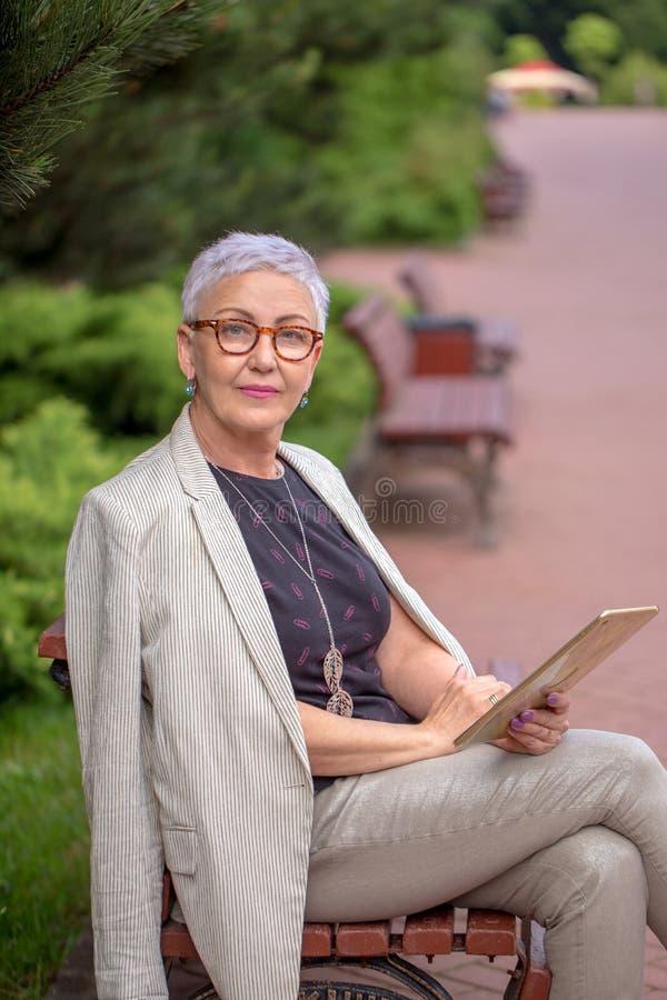 En elegant gullig kvinna studing på det netto i fyrkanten arkivfoton