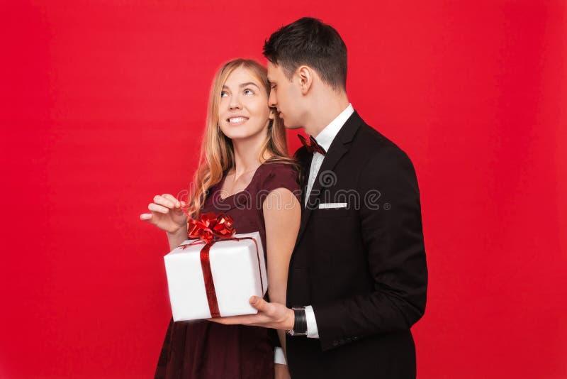 En elegant man i en dräkt ger en överraskning till en kvinna, ger henne en gåva, på en röd bakgrund, begreppet av kvinnors dag royaltyfri bild