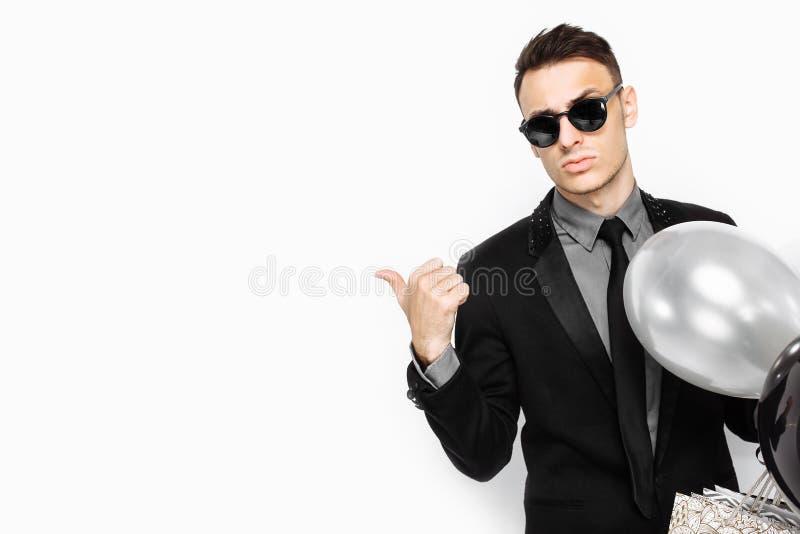 En elegant man i en svart dräkt, med påsar i hans händer och boll royaltyfri bild