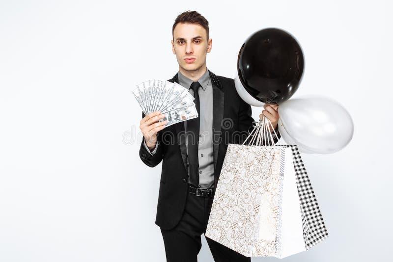 En elegant man, i en svart dräkt som rymmer påsar, för att shoppa, och arkivfoto