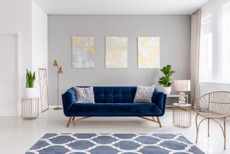 En elegant marinblå soffa i mitt av en ljus vardagsruminre med guld- metallsidotabeller och tre målningar på en grå färg arkivbilder