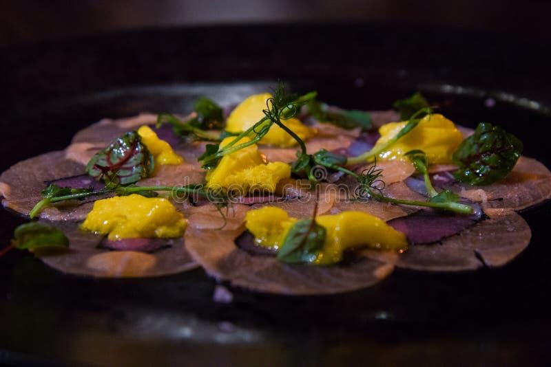 En elegant maträtt på en mörk platta royaltyfri bild