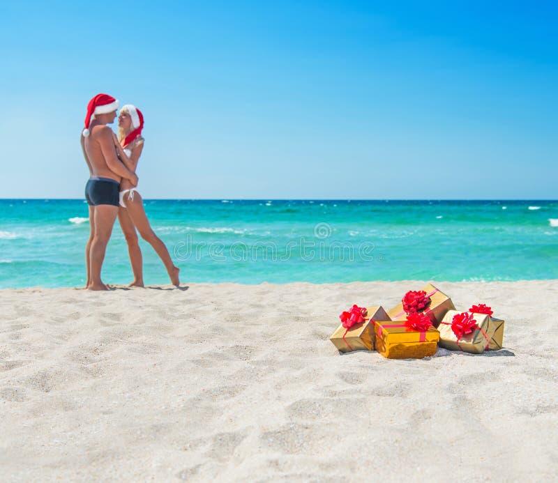 En embrassant des couples d'amants dans des chapeaux de Santa en mer échouez image libre de droits