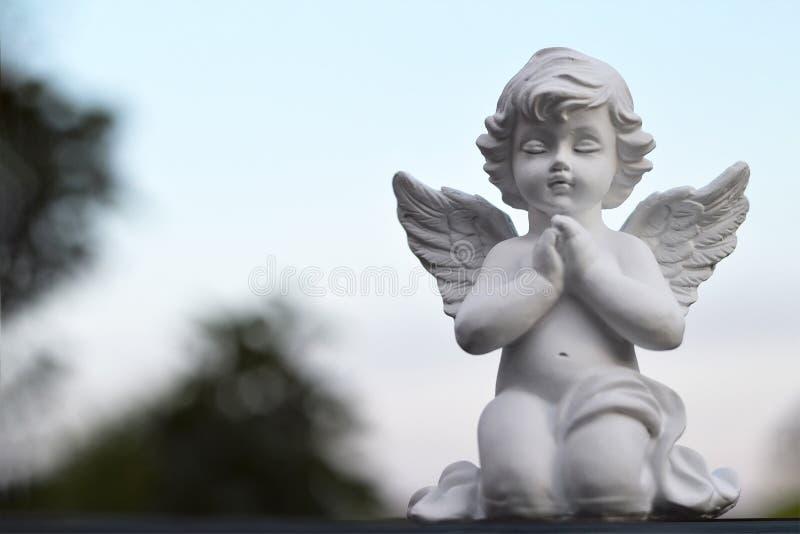 En engelenbeschermer die knielen bidden royalty-vrije stock foto's