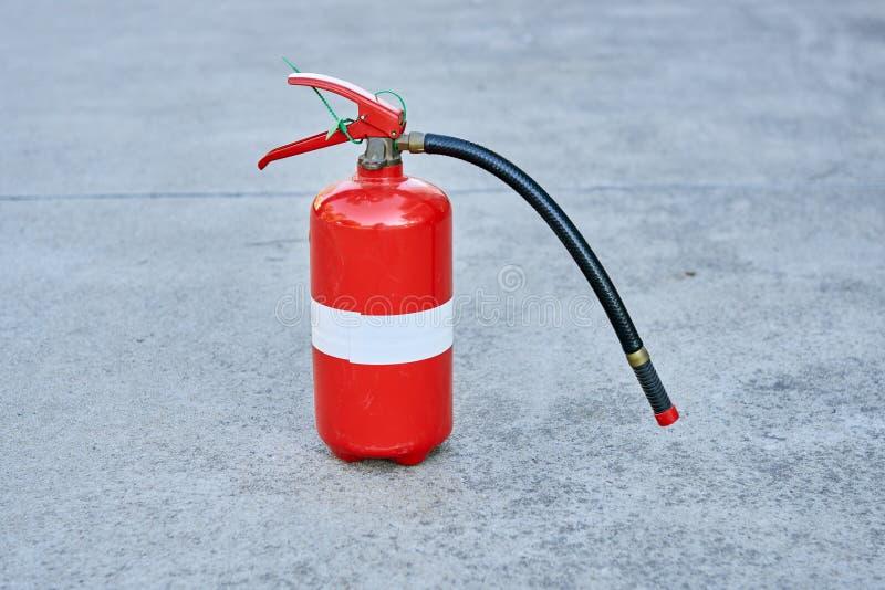 En enkel isolerad brandsläckare på betong i säkerhet som är röd med en vit bandremsa runt om mitt royaltyfri foto