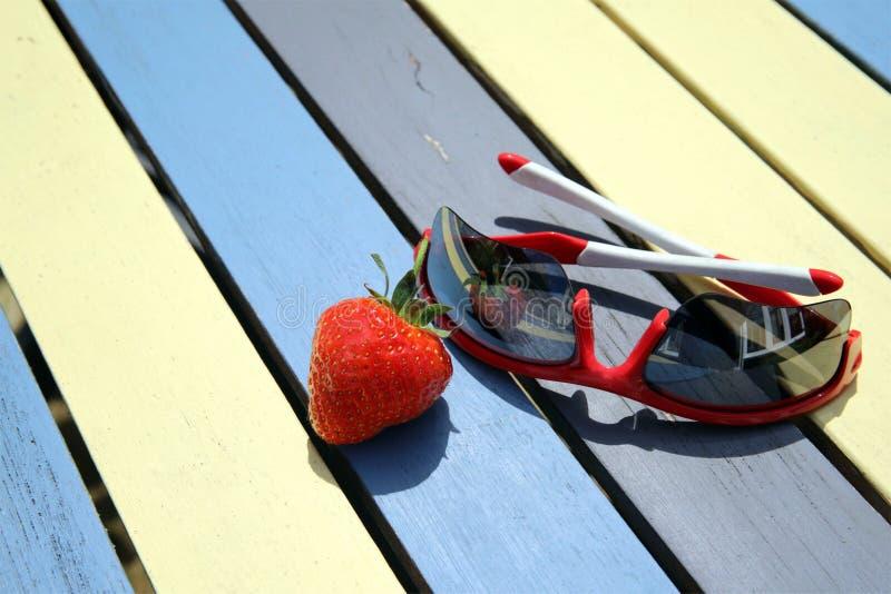 En enkel röd jordgubbe och ett par av solglasögon arkivbilder