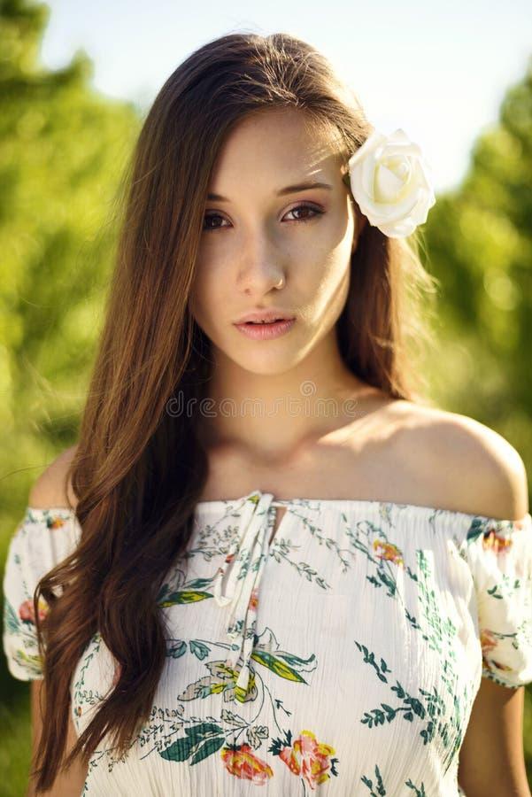 En enkel stående av en iklädd kvinna en klänning med den blom- modellen som omges av lugn och naturen som tänds av solstrålar arkivfoton