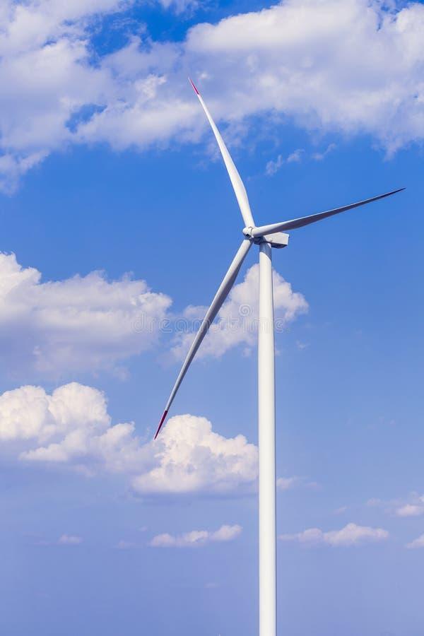 En enkel väderkvarnturbin med delvis molnig blå himmel i bakgrund förnybar turbinwind för energi arkivbild