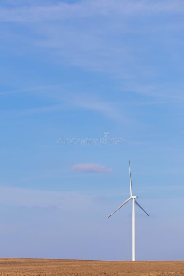 En enkel väderkvarnturbin på jordbruks- fält med blå himmel i bakgrund förnybar turbinwind för energi arkivbilder
