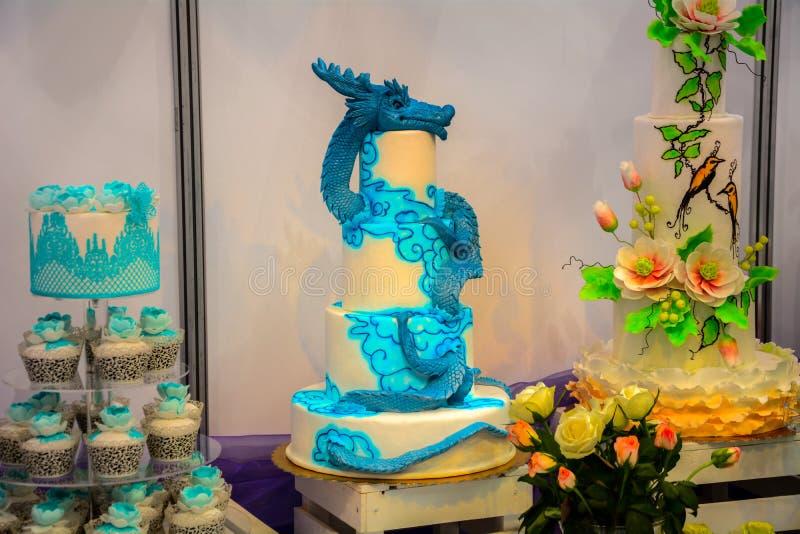 En enorm blå drake som bevakar bröllopstårtan arkivbilder
