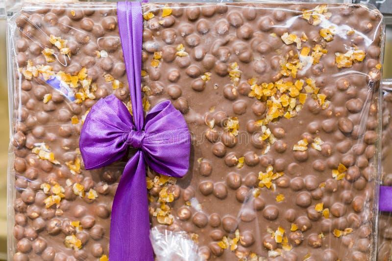 En enorm chokladstång som binds med ett band söt gåva choklad mjölkar muttrar royaltyfria foton