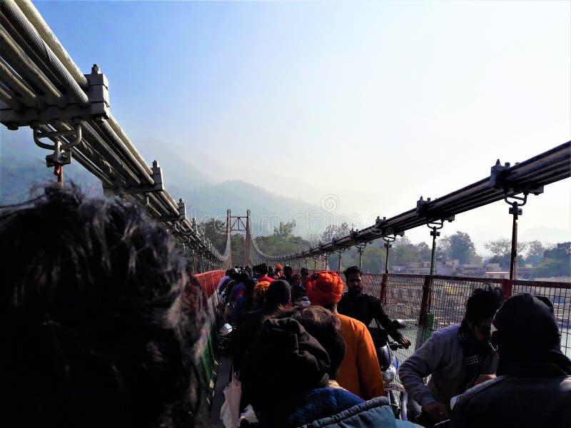 En enorm folkmassa som går till och med en Lakshman Jhula bro, Rishikesh, Indien arkivfoton