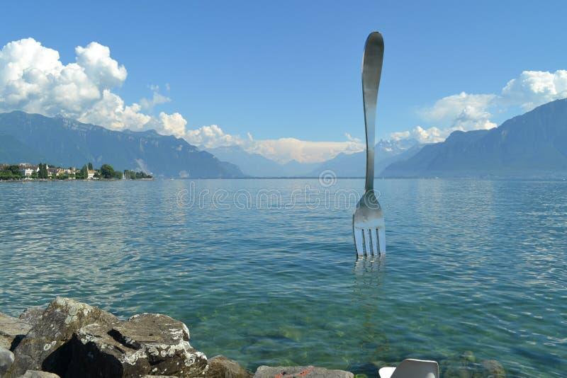 En enorm gaffel i sjöGenève Berglandskap, vaggar och turkosvatten arkivfoto