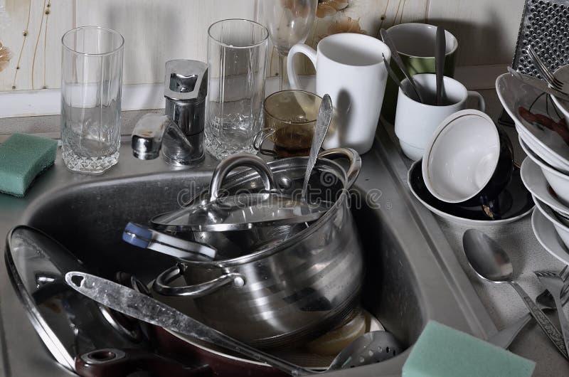 En enorm hög av odiskad disk i diskhon och på countertopen Många redskap och kökanordningar, innan tvätt royaltyfria bilder