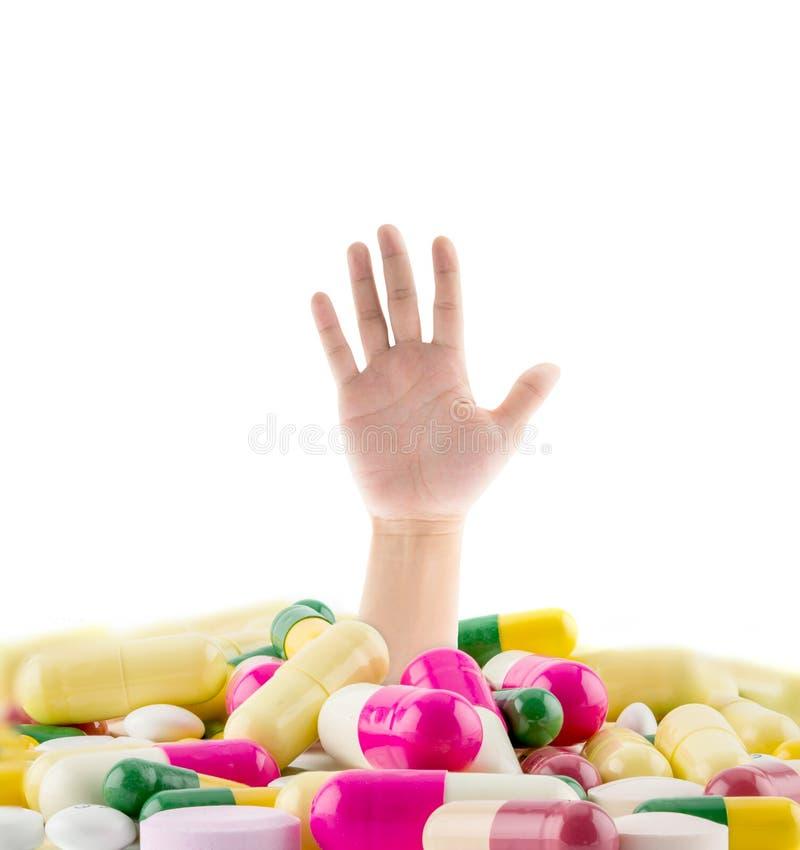 En enorm hög av olika preventivpillerar med en mans hand royaltyfri fotografi