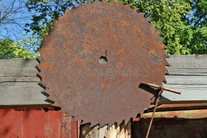 En enorm rostig cirkelsåg som hänger på ett lantligt staket royaltyfri bild