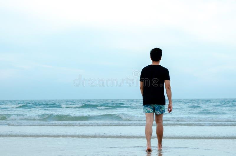 En ensam asiatisk man som bara går på stranden royaltyfri bild